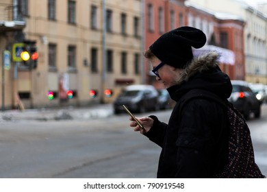 the man with the phone crosses the road