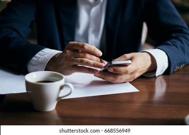 A man with a phone is drinking coffee