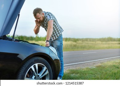 man with a phone in front of the open hood of a broken car