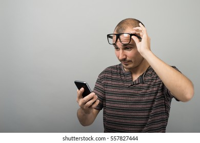 a man with a phone in glasses