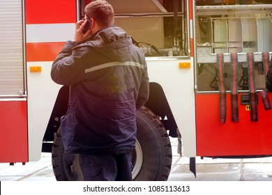 a man with a phone in his hands talking near a red fire engine with fire fighting equipment