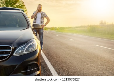 man with the phone on the road at the car