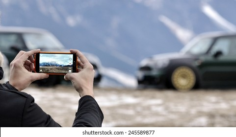 Man photographed mountains and parking cars in the new generation smart phone with snowy background in winter time.