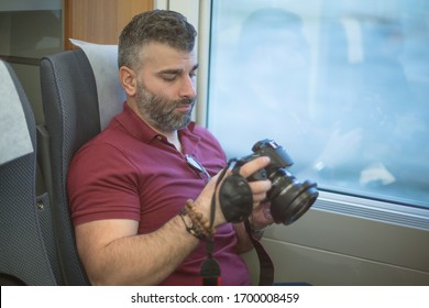 Man photographer with beard looking at the back camera screen