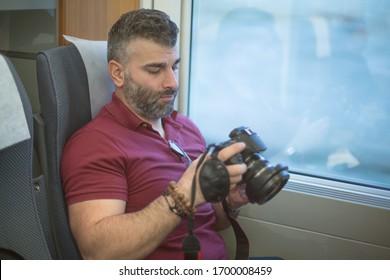 Hombre fotógrafo con barba mirando la pantalla de la cámara trasera