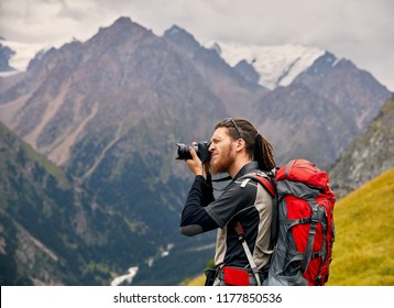 Man photographer with big backpack and camera taking photo of the mountains. Travel Lifestyle concept adventure active vacations outdoor