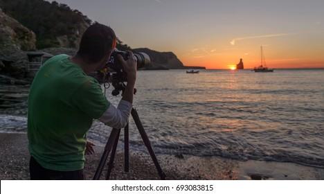 man photographer with camera on tripod sunset at sea on benirras beach , ibiza , baleares