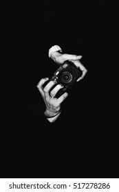 A man photographer holding a camera. Retro camera on a black background.