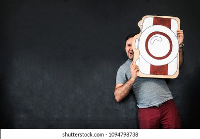 A man is a photographer with a large painted camera. Props. Funny Face. Dark gray background. Place for text. The photographer shoots at the camera. Picture of the camera. Focussed face. Profession.