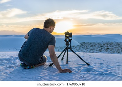 Man photographer sitting back with tripod camera in white sands dunes national monument park in New Mexico view of sunset