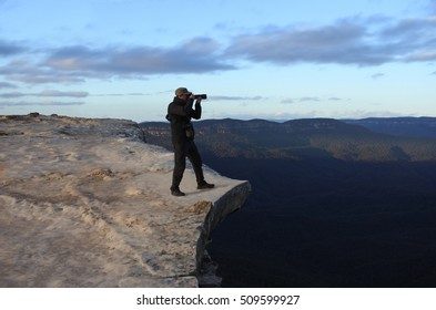 Man photographer stands on a cliff and photographing the landscape from Lincoln Rock Lookout at sunrise in the Blue Mountains National Park in the Blue Mountains region of New South Wales, Australia