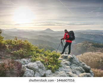 Man photographer taking picture of landscape when sunrise at mountain peak.Travel and hobbies concept.