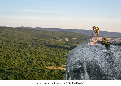A man photographer at the top of the mountain takes pictures of the landscape