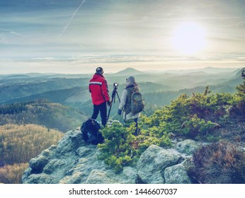 Man photographer and woman traveler  photographing with the camera on the tripod. Two people  takes a shot of the mist covered mountains and the rocks