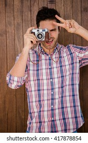 Man photographing with camera and making v sign on a wooden background