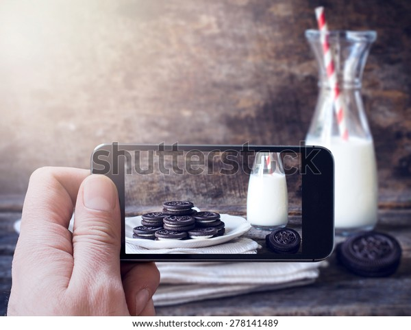 Man photographing cookies and bottle of milk with his mobile phone