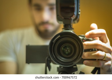 Man photographing with dslr camera, viewed from front, blurred.