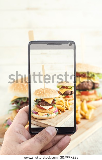 Man photographing with his cell phone camera big beef burgers