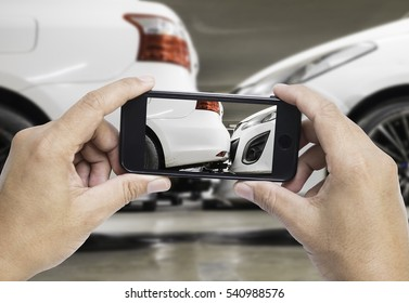 Man photographing his vehicle with damages for accident insurance with smart phone. The accident at the car park