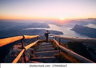 Man fotografiert Landschaft mit See und Bergen bei schönem Sonnenaufgang. Aussicht vom Monte Pilatus, Luzern, Schweiz