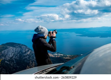 Man photographing lanscapes standing near his car on the top of mountain