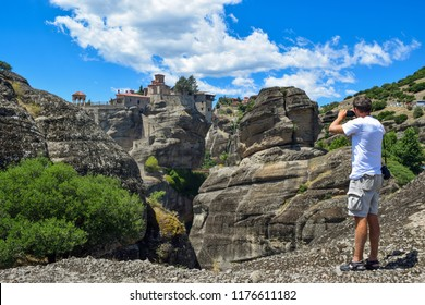 The man is photographing the monastery of St. Nicholas Anapavsas (Joyous) located on the rocks of Meteora in Greece.