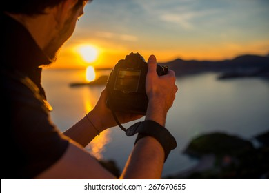 Man photographing with professional photo camera beautiful landscape on the sunset on the top of the mountain