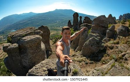 man photographing selfie on mountain background, tourism concept, horizontal photo