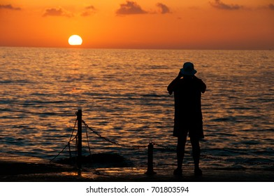man is photographing a sunset against the background of the sea.