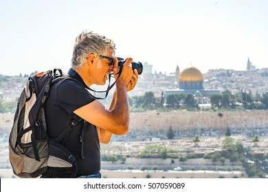 Man photographing tourists in Jerusalem with the background Mosque dome of the rock