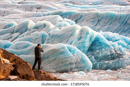 Man photographs the blue glacial ice at the Svinafellsjokul glacier in southeast Iceland. This is the largest ice cap in Europe.
