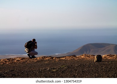 A man photographs an island in the ocean, squatting on the edge of a cliff.
