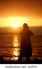 Man photographs the sunset at Viña del Mar, Chile.