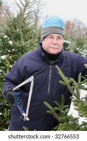 Man picking a Christmas Tree at a tree farm