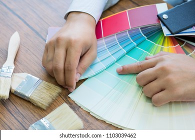 Man picking a color for her house walls, a professional painter and decorator is showing her color swatches