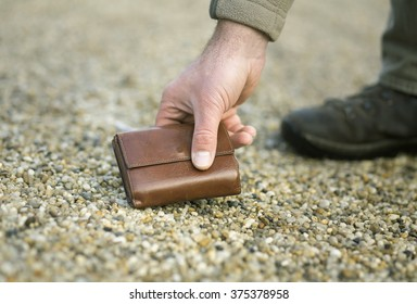 Man picking up fallen leather wallet on ground