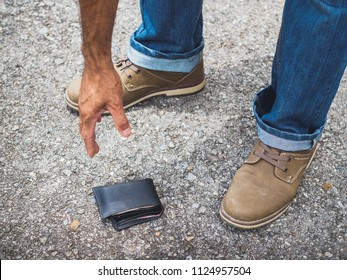 The man picking up a fallen wallet on the street. Lost money concept.