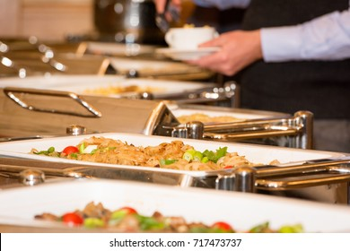 A man is picking food from a banquet table with chafing dish heaters on a festive event - selective focus on food in one heater