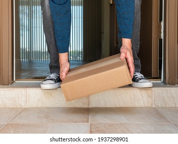 Man picking up a package box delivered to a residential doorstep. Online order package delivery to the front porch of home. - Shutterstock ID 1937298901