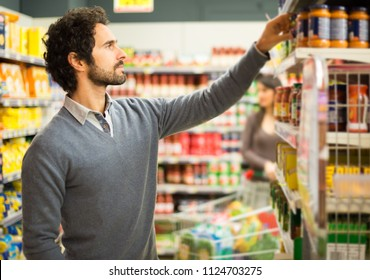Man picking up a product in a supermarket