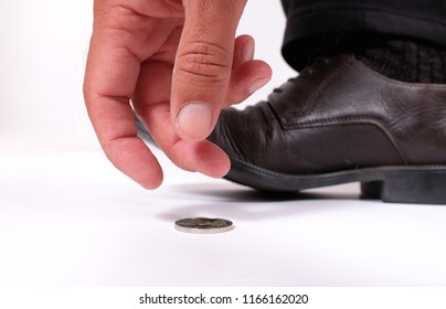 A man picks up found coin from the ground