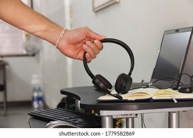 man picks up his earphone from his desk in the house wiht laptop place nearby