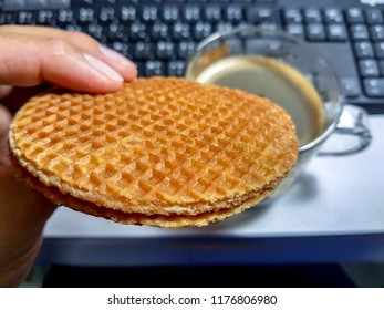 Man picks up stroopwafel to eat in front of woking table. Stroopwafel a famous waffle from dutch. Eat it with black coffee.