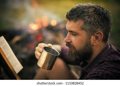 man at a picnic reading a book. Man traveler read and drink at campfire flame. Sustainable education, environment concept. Camping, hiking, lifestyle. Summer vacation, activity. Hipster hiker with