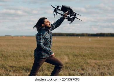Man pilot holding dji quadcopter drone in handand running at outdoor field