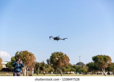 A man piloting a drone in the park in spring-summer time