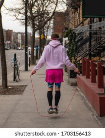 Man in Pink clothes skipping rope on street sidewalk