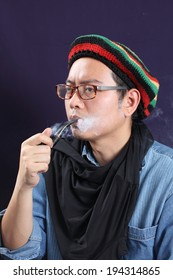 a man with a pipe in rastafarian hat