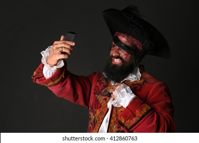 Man in a pirate costume with mobile phone, makes self