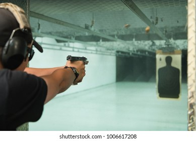 Man with pistol at firing range with target in background